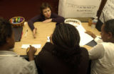 Lena Karabushin, (cq), center top back, kneeling at the table, is an instructor working closely...