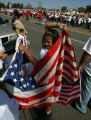 Jocelyn Gomez, 10, raps herself in an American Flag while preparing to march with her sister...