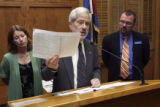Senator Bob Hagedorn, center, holds a spread sheet comparing drug prices making a point as...