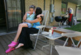 Kailya Goodman, CQ, 11, left, sits on her mother, Christine Goodman's lap during sensitive moment...