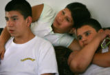 Ana Cortez, CQ, 30, center holds onto her two sons Jonathan Cortez, CQ, 12, right, and Victor...