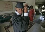 Broderick Bell (cq), 19, left, straightens his graduation cap in his Aurora home with his mother...