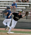 Brandon Tucker (2) tags safely at first base before Mike Goldstein (5) catches the ball. Columbine...