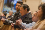 Adrian Jesus Hernandez, cq, 17, left, watches his father, Samuel Hernandez, cq, 47, pray during...
