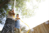 Ana Cortez, CQ, 30, and her son Jonathan Cortez, CQ, 12, waters the family garden at their home in...