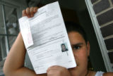 Jonathan Cortez, CQ, 12, holds paperwork with a photograph of himself at age seven that was taken...