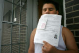 Jonathan Cortez, CQ, 12, holds paperwork and a photograph of himself at age seven that was taken...