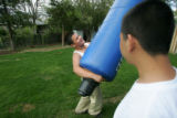 Jonathan Cortez, CQ, 12, left, plays with his brother Victor Cortez, CQ, 15, in their backyard at...