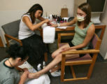 Patient Candi Holzer, (cq), 25 years old, right, gets a pedicure from Marrana Davis (cq - working...
