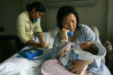 Pediatrician Dr. Sofia Aliaga, left, explains a consent for to Mun Song, CQ, right, through a...