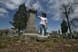 Jayne Uhlir (cq) examines one of the old headstones of the Smyth family from 1893 at Riverside...