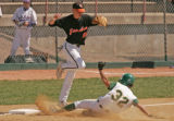 Grand Junction third baseman Eric Nordine leaps out of the way of Mountain Vista Golden Eagles...
