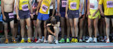 A runner drops to his knees to reflect and focus before the start of the Men's Citizen Race at the...