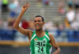 Ethiopian runner Berhanu Adane (#24) signals victory as he prepares to cross the finish line in...