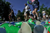 Empty cups litter the road as runners pass an AID station at Mile Five on Walnut Street of The...
