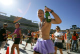 David Zakavec (cq), 22, of Fort Collins crosses the finish line with a bottle of champagne after...