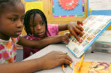 Third-graders Alliance Cooper (cq), 8, left, and Britney Wilson (cq), 8, right, look at a book...