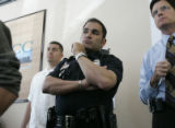 Denver police officer Robert P. Fitzgibbons, (cq) (center in uniform) listens to Rufino Trujillo...