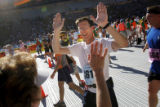 Tom Dunne (cq, center) high-fives his wife Monika (cq, left) after the two finished running the...