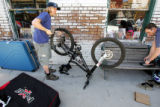 Mark Fidler (cq, center), 37, of Sheffield, England inflates his rear tire in downtown Fruita...