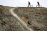"A pair of mountain bikers watch on as another drops down a steep incline on ""Zippety Do..."