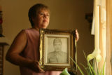 Yolanda Luna (CQ), 50, of Aurora, holds the photo of father-in-law Agustin Luna (CQ), 74, who died...