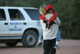 Teddi Gray carries her nephew Evan Thompson, an 8 year old boy who had been missing since early...