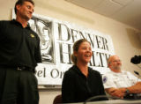 Dawn Green, cq, center, wife of injured firefighter Billy Green, flanked by Denver Fire Chief...