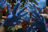 A sea of blue after glow on the hands of the contributing artists after they had placed their hand...
