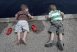 Riley Crownin (l) and his brother Dean Crownin, both 3, (they are two of triplets) stick their...