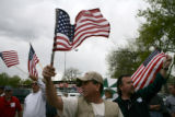 Twin brothers Larry (center) and Gary Wallace (cq), right, wave flags in Fort Collins Sunday,...