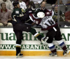 Dallas Stars Mike Modano (9 - left) tangles with Colorado's Ian Laperriere (14 - right) during...