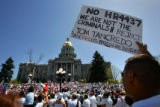 Juan C. Morales (cq, right), 29, of Denver holds a double-sided sign out front of the State...