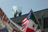 Two men hold anti-immigration signs as marchers in a pro-immigrant rally walk down Speer Blvd. in...