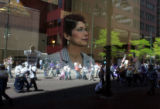 Patti Salas, cq, Denver, an employee at Cash Bank and Trust, watches as demonstrators march past...