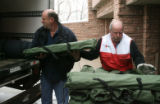 Red Cross worker Rick Curlin (cq), left, and Red Cross volunteer, Paul Madigan (cq), load cots...