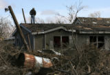 MJM342 Julio Salgado (cq) stands on the roof of his brother, Victor Salgado's damaged home in...