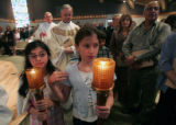 Servers Natalie Homsi (cq) left and Justine Moussallem(cq) , both 10, carry candles in a...