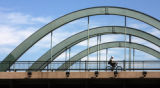 A man enjoys the nice weather as he rides his bike across a Speer Blvd. bridge, goes over Little...