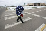 Engineer Dominick Zappia, (cq), of the Aurora Fire and Rescue Company caught the large flag used...