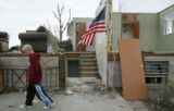 Kyle Dupree (cq), 12, walks past a ruined home flying the U.S. flag in Holly, Colo., Friday, March...