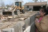 Rachel Ramos (cq) looks on as a crew tears down her home at Park Street in Holly, Colorado. Her...