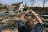Josh Haigh (cq) takes a picture on Sunday, April 15, 2007, of the the wreckage of a house which...