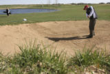 Jennifer Barnett, left, watches as Bill Swearingen hits out of the sandtrap. *(the ball is...