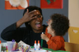 Lesley Brooks, cq,  joins her son August Brooks-Johnson, 2 1/2, during craft time as they...