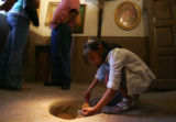 Maria Mendoza (cq), 10, collects holy soil at the Chimayo Sanctuary, on Wednesday, April 4, 2007. ...