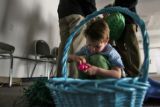DLM6113  Cooper Kramis, 4, of Erie cracks open one of the Easter eggs he got while participating...