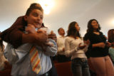 (from left) Luis Jacobo (cq) hugs his friend Erik Romero (cq) at the Iglesia Cristiana La Roca in...
