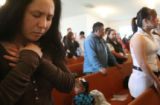Tammie Martinez (cq) (center left) joins in silent prayer at the Iglesia Cristiana La Roca, as the...