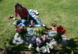 Patricia DePooter (cq), mother of Corey DePooter (cq), sits in thought after placing flowers for...